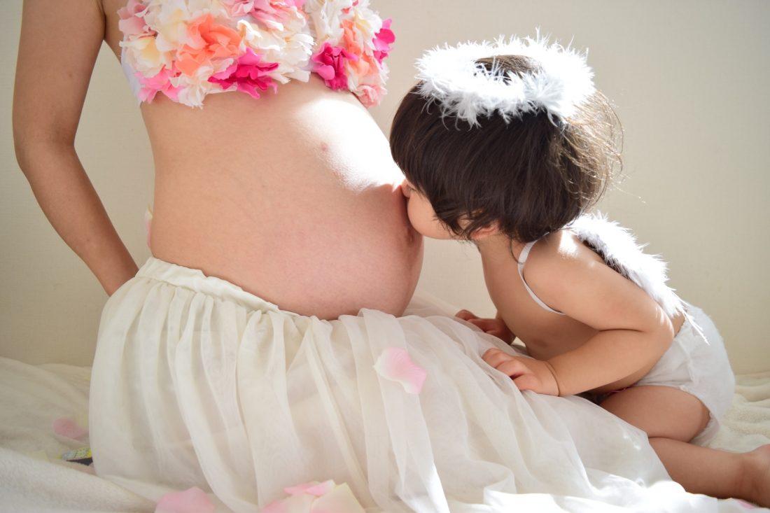 妊婦さんのお腹にチューする子どもの写真