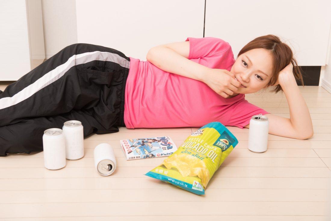 お菓子をぼりぼり食べている妊婦の写真