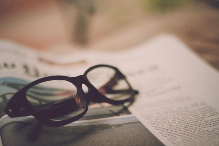 新聞の上に眼鏡を乗せている写真
