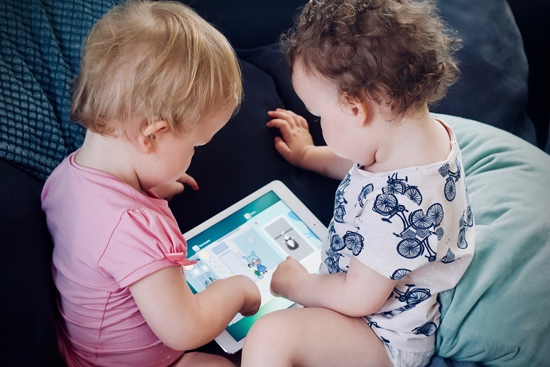 友だちと一緒に動画を見ている赤ちゃんの写真